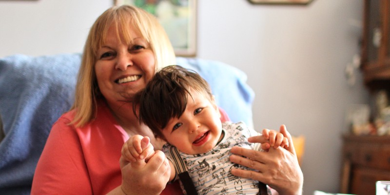 Pretty blond woman with bangs in a coral coloured t-shirt, smiling while trying to hold onto a cranky toddler.