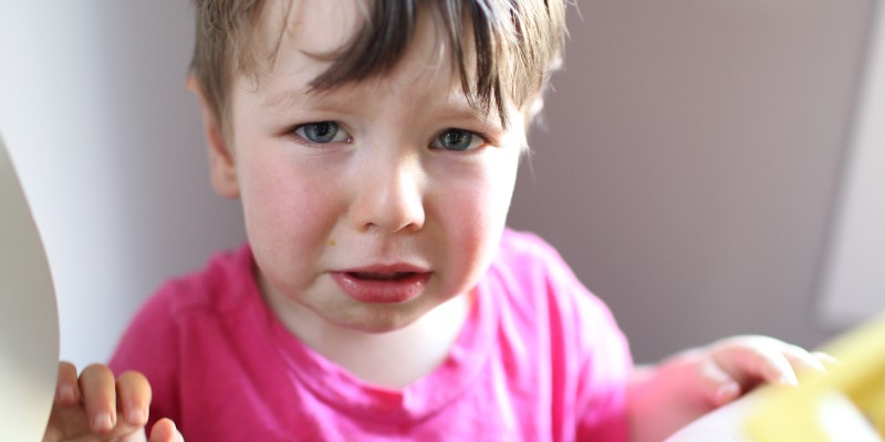 Toddler in a pink shirt making a very sad face.