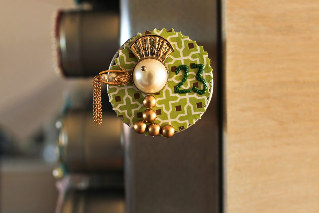 A gold partridge with a mohawk hairdo made out of beads. The number 23 is on it in green sparkly paint.