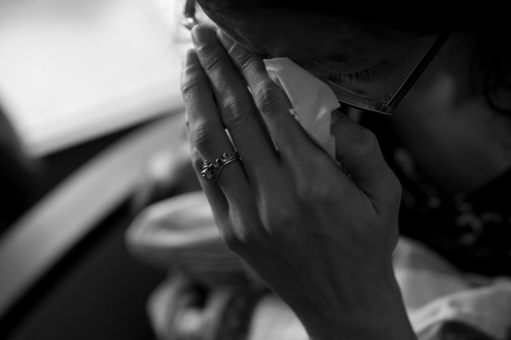 Woman holding her hand to her face, crying into a tissue.