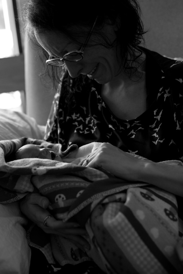 A woman holds a still born baby girl in her arms. She is crying and trying to get the baby's hand inside her blanket.