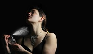 Woman spraying perfume cloud at herself in the shape of a skull and cross bones.